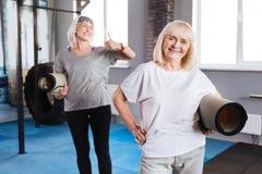 Femmes heureuses joyeuses se tenant avec des tapis de yoga Photographie stock