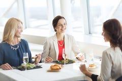 Femmes heureuses mangeant et parlant au restaurant Photographie stock libre de droits