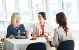 Femmes heureuses mangeant et parlant au restaurant Images stock