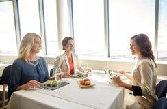 Femmes heureuses mangeant et parlant au restaurant Image stock