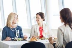 Femmes heureuses mangeant et parlant au restaurant Photographie stock