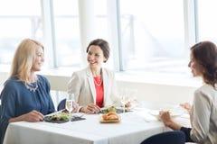 Femmes heureuses mangeant et parlant au restaurant Images libres de droits