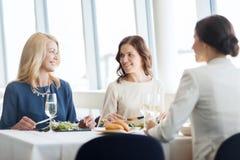 Femmes heureuses mangeant et parlant au restaurant Image libre de droits