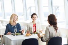 Femmes heureuses mangeant et parlant au restaurant Photos libres de droits