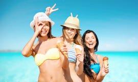 Femmes heureuses mangeant la crème glacée au-dessus de la mer et du ciel Photos stock