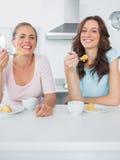 Femmes heureuses mangeant le gâteau et ayant le café ensemble photos stock