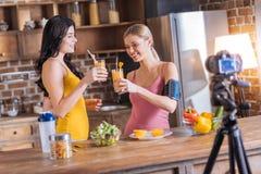 Femmes heureuses positives buvant du jus frais Images libres de droits
