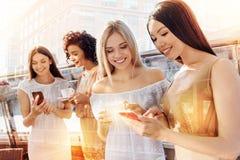 Femmes heureuses positives regardant le smartphone Image stock