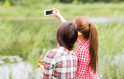 Femmes heureuses prenant le selfie par le smartphone dehors Photographie stock libre de droits