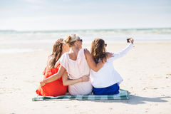 Femmes heureuses prenant le selfie par le smartphone sur la plage Photos stock