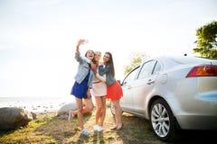 Femmes heureuses prenant le selfie près de la voiture au bord de la mer Photographie stock libre de droits