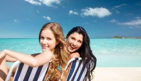 Femmes heureuses prenant un bain de soleil dans les chaises sur la plage d'été Image stock
