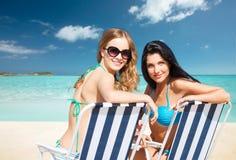 Femmes heureuses prenant un bain de soleil dans les chaises sur la plage d'été Photo stock