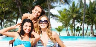 Femmes heureuses prenant un bain de soleil dans les chaises sur la plage d'été Photographie stock