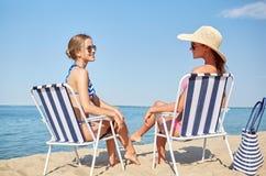 Femmes heureuses prenant un bain de soleil dans les salons sur la plage Images stock