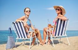 Femmes heureuses prenant un bain de soleil dans les salons sur la plage Image stock