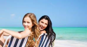Femmes heureuses prenant un bain de soleil sur des chaises au-dessus de plage d'été Photo stock