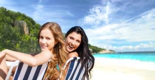 Femmes heureuses prenant un bain de soleil sur des chaises au-dessus de plage d'été Image stock