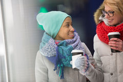 Femmes heureuses regardant l'un l'autre tout en tenant les tasses jetables Image stock