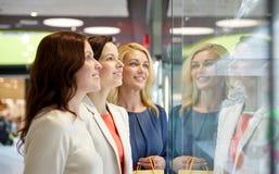 Femmes heureuses regardant la fenêtre de boutique de bijoux dans le mail Image stock