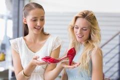 Femmes heureuses regardant une chaussure de talon Image stock