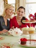 Femmes heureuses s'asseyant à la table de salle à manger Photos stock