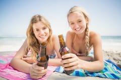 Femmes heureuses se trouvant sur la plage avec la bouteille à bière Photographie stock libre de droits