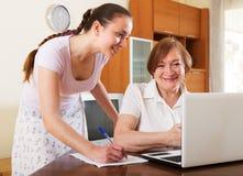 Femmes heureuses semblant les documents financiers dans l'ordinateur portable Image libre de droits