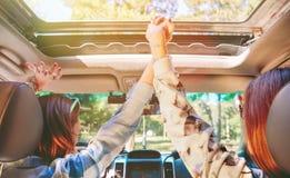 Femmes heureuses tenant des mains et soulevant des bras à l'intérieur Photographie stock libre de droits