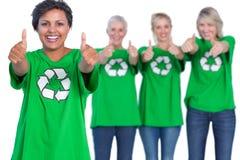 Femmes heureuses utilisant les T-shirts de réutilisation verts renonçant à des pouces photos stock
