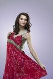 Femmes heureux essayant la robe rouge de fleur Images stock