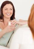 Femmes heureux s'asseyant sur un sofa avec des tasses Image stock