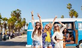 Femmes hippies montrant la paix au-dessus de la voiture de monospace en La Photo libre de droits