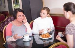Femmes inquiétées buvant du café dans le cafétéria Image stock