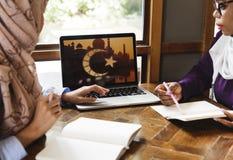 Femmes islamiques discutant et à l'aide de l'ordinateur portable pour le travail Images libres de droits