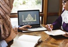 Femmes islamiques discutant et à l'aide de l'ordinateur portable pour le travail Photographie stock