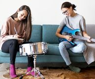 Femmes jouant la musique ensemble à la maison Images stock