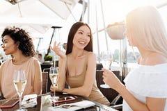 Femmes joyeuses avec plaisir parlant entre eux Images stock