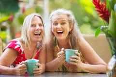 Femmes joyeuses s'asseyant dehors Photographie stock