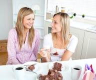 Femmes joyeux mangeant un gâteau de chocolat Image libre de droits