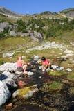 Femmes lavant des paraboloïdes dans le flot de montagne images libres de droits