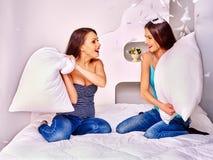 Femmes lesbiennes aux combats d'oreiller dans le lit Photos stock
