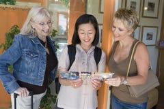 Femmes lisant la brochure de la station de vacances Image libre de droits