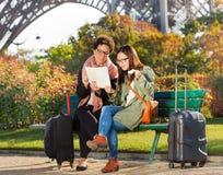 Femmes lisant la carte de Paris et goûtant des macarons Image stock