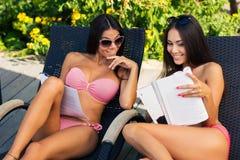 Femmes lisant le magazine sur la chaise longue Image stock