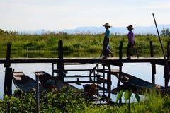 Femmes locales marchant sur le pont en bois Village de Maing Thauk Lac Inle myanmar images libres de droits