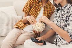 Femmes méconnaissables regardant la TV à la maison Image libre de droits