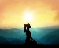 Femmes méditant sur la haute montagne à l'arrière-plan de coucher du soleil Photographie stock libre de droits