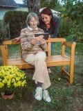 Femmes mûres et supérieures à l'aide d'un comprimé dans le jardin Photographie stock libre de droits