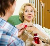 Femmes mûres avec la médecine liquide d'intérieur Image libre de droits